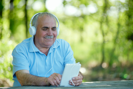 downloaded: Senior man searching for an online or downloaded tune on his MP3 player or tablet as he sits outdoors in the garden wearing a set of headphones concentrating on the screen