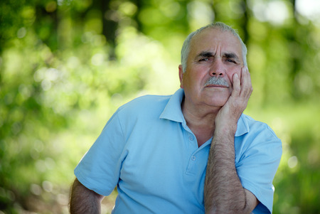Elderly grey-haired retired man with a moustache sitting outdoors in a lush green park smiling at the camera photo