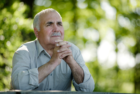 introspective: Elderly man sitting in the garden at a wooden table thinking and staring into the distances as he reminisces fond memories, with copyspace