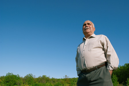 Low angle view of an overweight senior man standing with his hands in his pockets against a blue sunny sky in the countryside accentuating his belly Reklamní fotografie