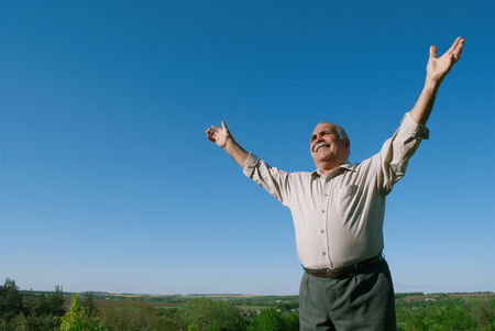 outspread: Happy senior man rejoicing in nature standing in open countryside against a sunny blue sky with his arms outspread and a joyful smile, with copyspace
