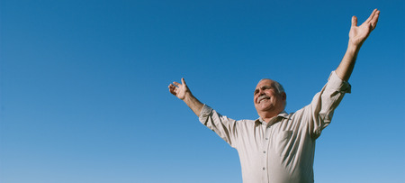 outspread: Happy joyful elderly man embracing the sun standing outdoors under a clear sunny blue sky with his arms outspread as he rejoices in nature, with copyspace Stock Photo