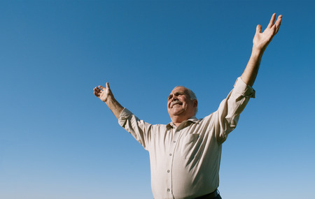 Senior retired man rejoicing in the sunshine standing under a clear blue sunny sky with his arms outspread and a beautiful joyful smile on his face, with copyspace