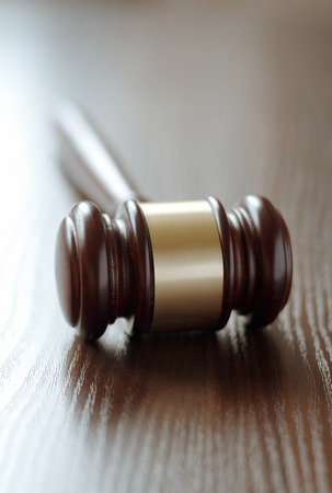 impartiality: Wooden judges gavel with a central brass band around it lying with the handle facing away on a wooden desk or table with shallow dof conceptual of law enforcement and judgements in court
