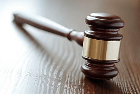 judgements: Wood and brass judges gavel standing upright on a wooden desk or table with the handle angled away and focus to the head, shallow dof with copyspace conceptual of judgements and court