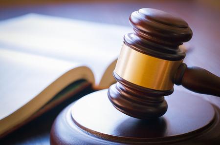 martillo juez: martillo marr�n y libro abierto sobre una mesa de madera de la ley en la sala del tribunal