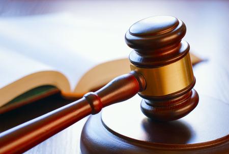 abogado: martillo marrón y libro abierto sobre una mesa de madera de la ley en la sala del tribunal