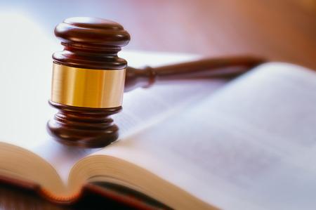 bruine hamer en een open boek op een houten tafel van de wet in de rechtszaal