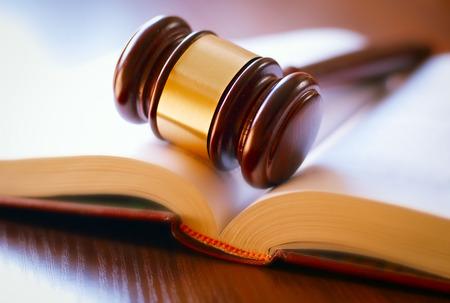 marteau brun et livre ouvert sur une table en bois de la loi dans la salle d'audience