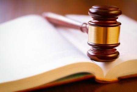 Bruine hamer en een open boek op een houten tafel van de wet in de rechtszaal Stockfoto - 29187184