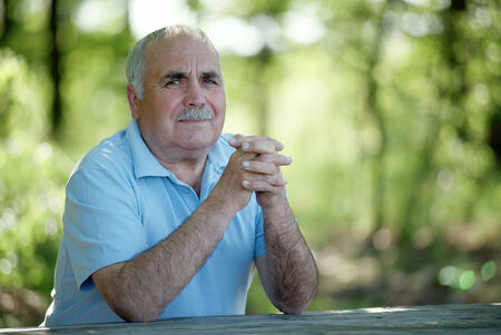 Elderly grey-haired retired man with a moustache sitting outdoors in a lush green park smiling at the camera