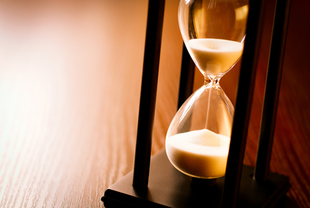 Hourglass with the sand running through in a wood frame on a wooden surface with shine and copyspace Stock Photo