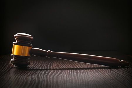 Wooden gavel with an ornamental brass band standing upright sideways on a textured dark wood surface conceptual of a judge or auctioneer