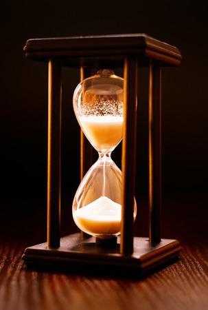 cronologia: Reloj de arena iluminada en un marco de madera con arena que entraba por entre las bombillas de vidrio que mide el tiempo que pasa sobre un fondo oscuro