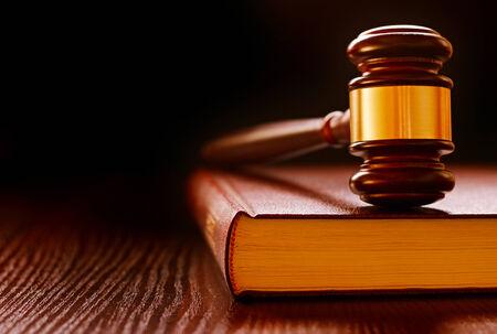 derechos humanos: Madera y latón jueces martillo de pie sobre un libro de leyes conceptual de aplicación de la ley y de las sentencias en los tribunales Foto de archivo