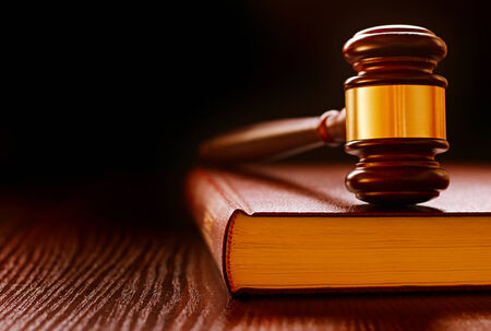 human rights: Wood and brass judges gavel standing upright on a law book conceptual of law enforcement and judgements in court Stock Photo