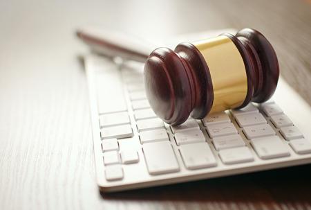 オンライン オークションや法執行機関の概念コンピューターのキーボードの上に横たわる、真鍮装飾が施された木製の小槌
