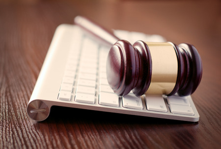 online auction: Wooden judges gavel on a computer keyboard, receding view with focus to the head with its brass decoration conceptual of online law enforcement and auctions
