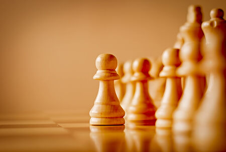 Low angle view across the surface of a chess board of a single wooden pawn in a chess game standing in front of the rest of the set in a game of skill, with copyspace photo