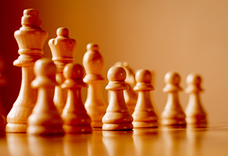 Chess set on a wooden chess board with the pieces lined up on two receding oblique lines with focus to a central pawn in the front row and copyspace, low angle view photo