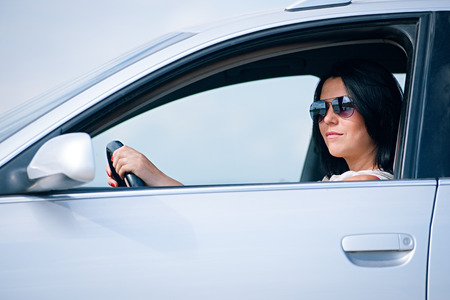 touring car: Beautiful young woman driving a car, side view Stock Photo