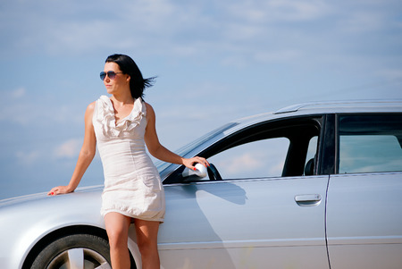 Beautiful young girl standing near the car against the sky photo