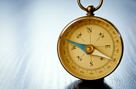 puntos cardinales: Cierre de vista de una brújula magnética portátil con copyspace mostrando la aguja, rosa de los vientos y los puntos cardinales conceptuales de la planificación, la navegación, el descubrimiento, los viajes y la estrategia