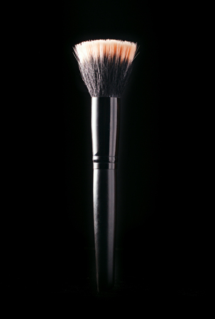 Close up of the head and soft bristles of a cosmetics applicator brush highlighted against a dark background with copyspace