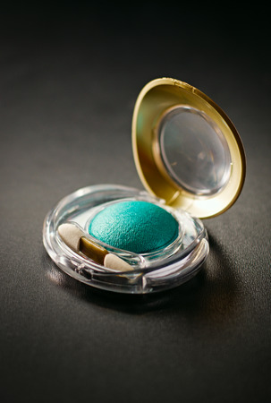 Colorful modern green eye shadow in a small compact with an applicator on a dark background in a beauty and cosmetics concept photo