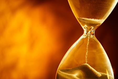 sand clock: Sabbia passando per le lampadine di vetro di una clessidra misurando il tempo che passa, come si conta fino a un termine o di chiusura su uno sfondo giallo con copyspace