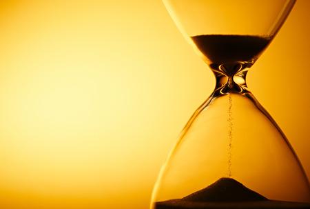 Zand die door de glazen bollen van een zandloper meten van het verstrijken van de tijd als het telt af naar een deadline of sluiting op een gele achtergrond met copyspace