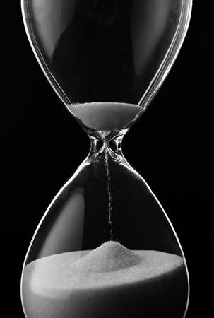 paciencia: Arena que se ejecuta a través de los bulbos de un reloj de arena que mide el tiempo que pasa en una cuenta atrás para una fecha límite, sobre un fondo oscuro con copyspace