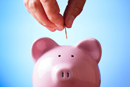 financial security: Close up view of the hand of a man placing a coin into the slot of a piggy bank in a savings and investment concept
