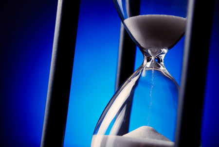 Egg timer or hourglass with blue sand running through the glass bulbs in a concept of passing time and time management