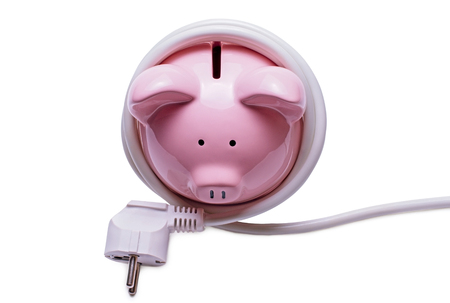 plug in: Online banking and savings concept with a pink ceramic piggy bank standing coiled in a white computer cord and plug isolated on a white background
