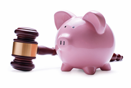 restitution: Porcelain pink piggy bank next to a wooden judge gavel, concept of savings, economic litigations and auctions, close-up with shadow on white