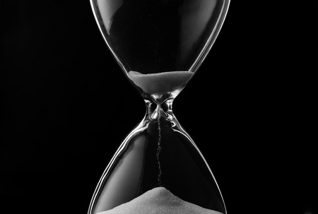 sands of time: Sand trickling through the bulbs of an hourglass or egg timer measuring the passage of time on a dark background