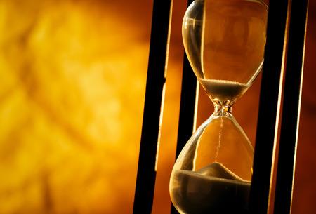 Image conceptuelle de mesurer le temps qui passe avec une vue rapprochée de sable qui traverse un sablier ou oeuf minuterie sur un fond d'or avec copyspace