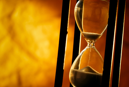 Conceptual image of measuring passing time with a close up view of sand running through an hourglass or egg timer on a golden background with copyspace Archivio Fotografico