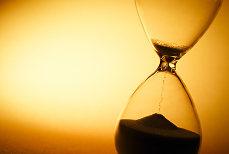 sand timer: Sand passing through the glass bulbs of an hourglass measuring the passing time as it counts down to a deadline or closure on a yellow background with copyspace Stock Photo