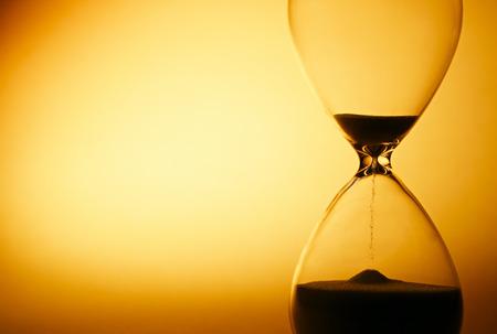 Sand, die durch die Glaskolben einer Sanduhr Messung der Durchlaufzeit, wie sie zählt zu einem Termin oder Schließung auf einem gelben Hintergrund mit Exemplar