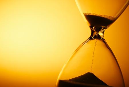 지나가는 시간을 측정하는 모래 시계의 유리 전구를 통과 한 모래는 마감일이나 클로저와 함께 copyspace가있는 노란색 배경에 카운트됩니다.