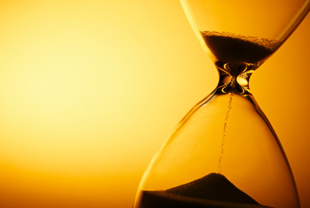 Sand passing through the glass bulbs of an hourglass measuring the passing time as it counts down to a deadline or closure on a yellow background with copyspace Standard-Bild