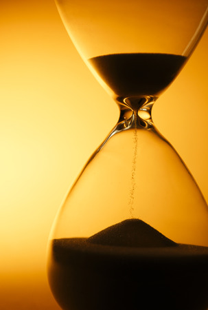 Sand passing through the glass bulbs of an hourglass measuring the passing time as it counts down to a deadline or closure on a yellow background with copyspace photo