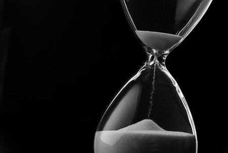 reloj de arena: Arena que se ejecuta a través de los bulbos de un reloj de arena que mide el tiempo que pasa en una cuenta atrás para una fecha límite, sobre un fondo oscuro con copyspace