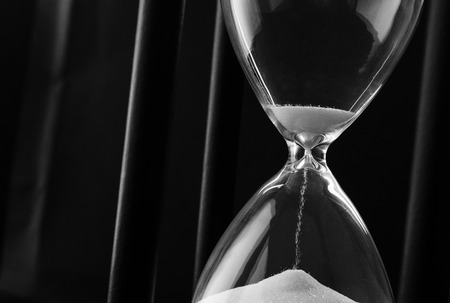 hourglass: Sand running through the bulbs of an hourglass measuring the passing time in a countdown to a deadline, on a dark background with copyspace