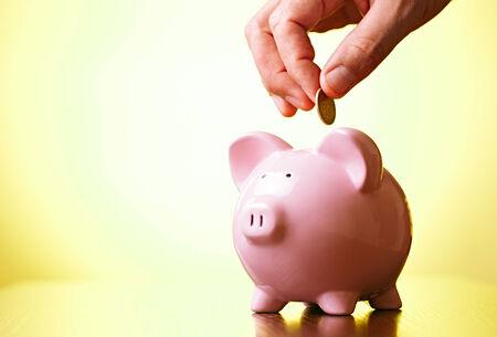 cuenta bancaria: Hombre que paga en dinero en una alcanc�a de colocar una moneda en la ranura con cuidado sobre un fondo amarillo se gradu� con copyspace, conceptual de las finanzas, el ahorro y la inversi�n Foto de archivo