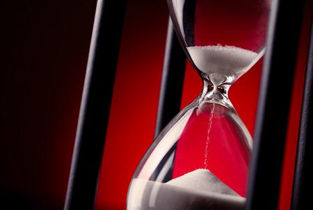 통과 시간과 시간 관리의 개념적 이미지에서 졸업 빨간색 배경에 달걀 타이머 또는 모래 시계