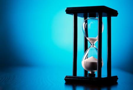 달걀 타이머 또는 시간과 시간 관리를 전달하는 개념적 이미지에서 copyspace와 졸업 파란색 배경에 모래 시계
