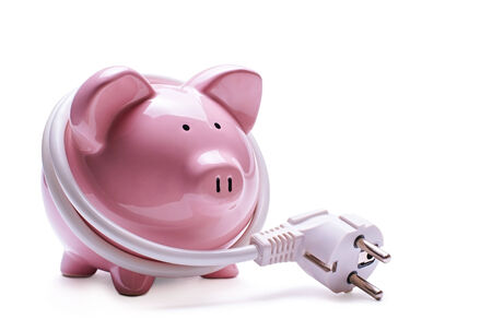 current account: Online banking and savings concept with a pink ceramic piggy bank standing coiled in a white computer cord and plug isolated on a white background